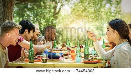 Happy students having barbecue on summer day in backyard home garden - Young cheerful people eating tasty bbq dinner - Concept about positive mood with friends - Focus on right blond man - Warm filter
