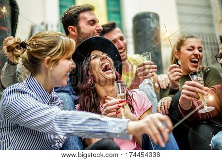Loud happy friends making party with champagne confetti and sparklers outdoor - Young people celebrating birthday drinking and laughing - Fest concept - Focus on center girl with hat - Warm filter