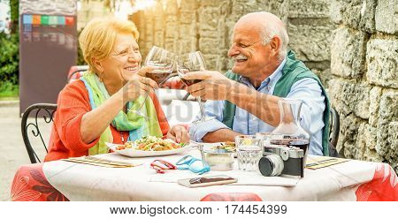 Happy senior couple cheering with red wine in italian restaurant outdoor - Old people having fun in vacation holidays eating lunch with back light - Love concept - Main focus on him - Warm filter