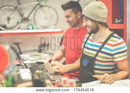 Two bicycle repairer colleagues working in bike garage - Positive mood bmx seller using computer in workshop - Retail selling and sport trend concept - Focus on right man face - Warm filter