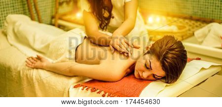 Young woman having back therapy massage in spa resort hotel salon - Female enjoying relaxing thai massage - Body care skin care wellness and chilling concept - Focus her eye - Warm filter