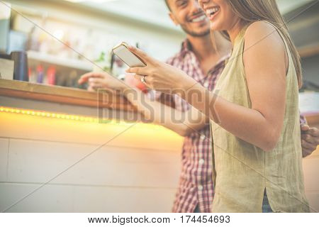 Happy smiling couple looking mobile smartphone cocktail bar outdoor - Young people having fun using mobile cell phone - Happiness and technology concept - Warm cinematic filter - Focus on woman hand
