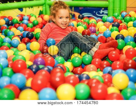 Cheerful child playing inside ball pit swimming pool - Little girl having fun in baby playground indoor - Childhood concept - Focus on female face - Warm filter