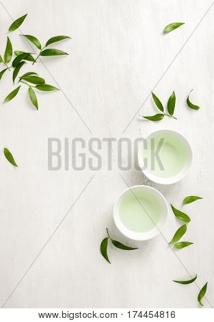 Tea concept two white cups of tea surrounded with green tea leaves view from above space for a text