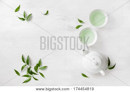 Tea concept two white cups of tea and teapot surrounded with green tea leaves view from above space for a text