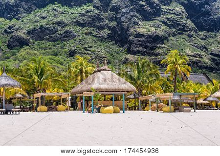 Le Morne Mauritius - December 11 2015: People are relaxing on the tropical Le Morne beach with coconut palms one of the finest beaches in Mauritius. Le Morne Brabant mountain in the background.