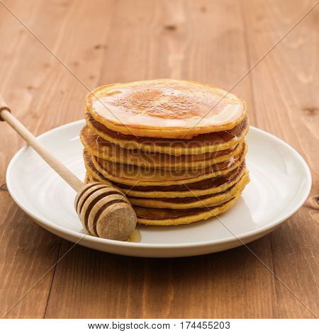 Vegan butternut squash puree pancakes on white plate with honey. Healthy gluten free breakfast on wooden table vegan pancakes butternut squash pumpkin puree healthy breakfast maple syrup honey golden yellow orange brown dessert stacked homemade food meal