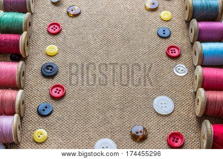 sewing tools (many different colorful thread many different buttons) on wooden background