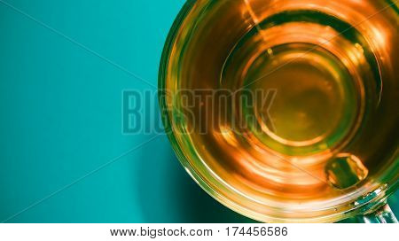Golden tea in transparent cup over blue background. Macro top view