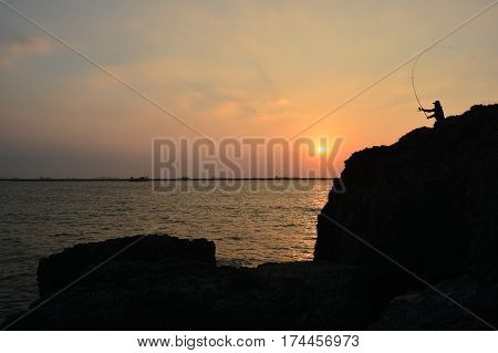 A fisherman casts his rod as sunset approaches at Kaohsiung, Taiwan