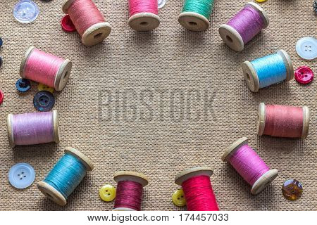 sewing tools (many different colorful thread different buttons) on wooden background