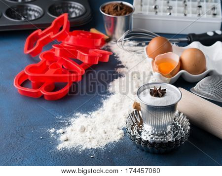 Baking tools rolling pin, sifter, letter moulds. Sweet food cake cookie dough ingredients on dark blue background
