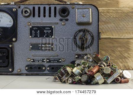 Retro voltage regulator. Old vintage electric stabilizer with transistors, resistors, radio parts wood backgraund.