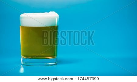 Foamy beer or ale in drinking glass over blue background. Front view