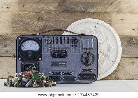 Vintage voltage regulator with transistors, resistors, radio parts and old plaster rosette wooden backgraund.