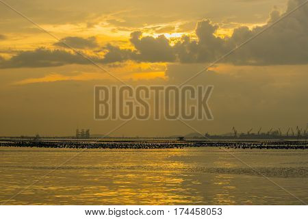 The atmosphere of the evening sea with cranes and cargo ships.