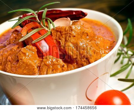 Stew - beef goulash in white bowl on table close-up