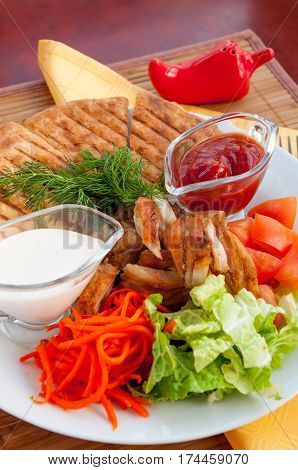Doner kebab on a plate with vegetables and salad.
