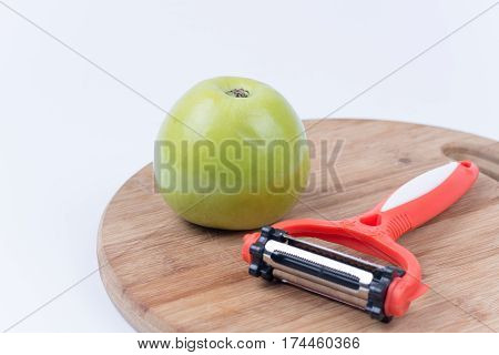 Green Apple And Plastic Peeler On The Kitchen Board