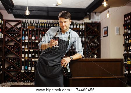 Male sommelier tasting red wine in cellar. Professional degustation expert appreciate quality of wine. Winemaker with bocal of alcohol drink and bottle in other. Profession in winemaking.