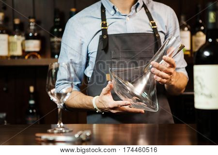 Wineglass at bar counter at background of sommelier with emty decanter. Glass carafe mixing bowl at the hands of waiter. Bartender at workplace