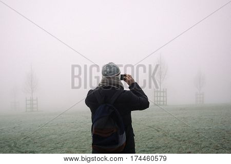 Young man dressed in winter coat, hat and scarf taking photo with mobile phone of Broomfield Park, London, disappearing in fog on cold winter morning.