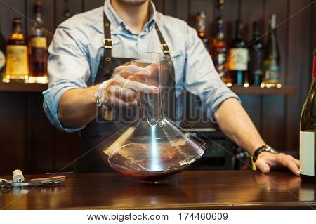 Sommelier shaking glass wine carafe to make perfect color of red wine. Male waiter holds decanter with alcohol beverage at bar counter. Bartender decanting wine without disturbing the sediment