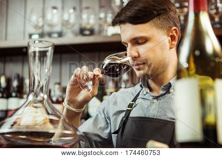 Male sommelier tasting red wine at bar counter. Bottle of wine nearby. Professional expert appreciates quality of alcoholic beverage, degustation process