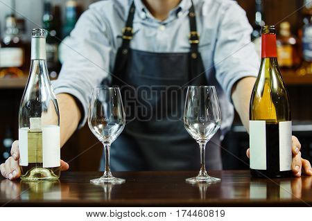 Male sommeliers holds white and red wine. The waiter with two bottles of liquor. The bartender behind the bar
