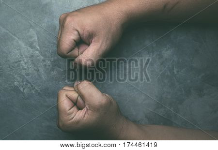 clenched fists of man on cement floor background.