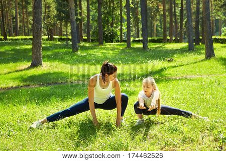 sporty mother and daughter. woman and child training in the park. outdoor sports. healthy sport lifestyle. fitness, yoga