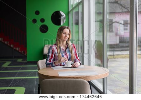 the girl in the café sitting alone prevents coffee