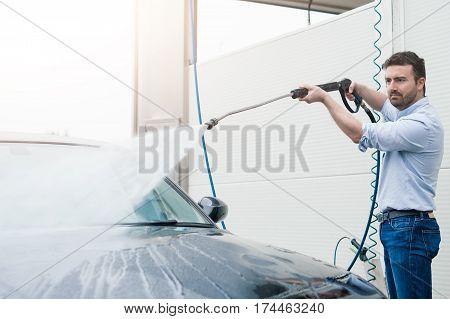 Man washing his car in a self-service car wash station