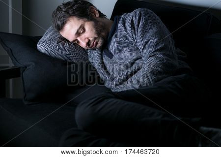 Man tired and depressed lying on the couch