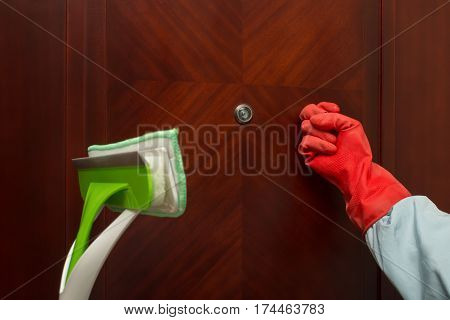 man with brush and glove knocking door concept of domestic cleaning