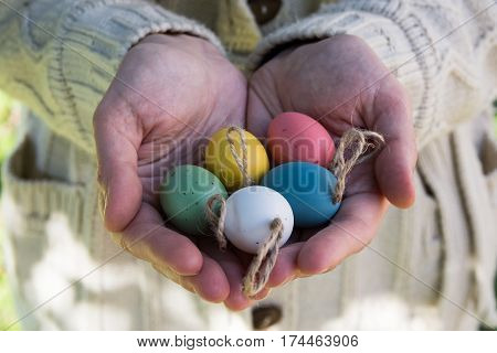 Young woman holding in hands decorative colorful Easter eggs on twine outdoors sun flecks closeup kinfolk style authentic