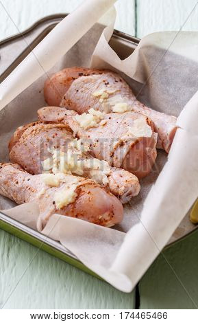 Unprepared poultry shins on plate at white wooden table