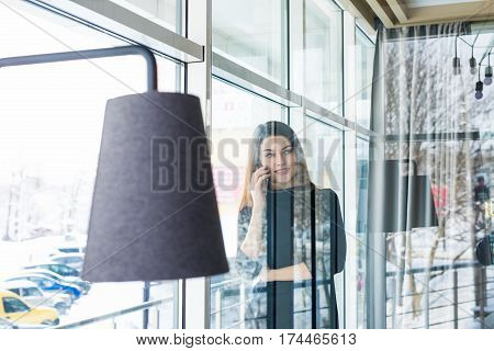 View though the window beautiful woman having cell telephone conversation in coffee shop