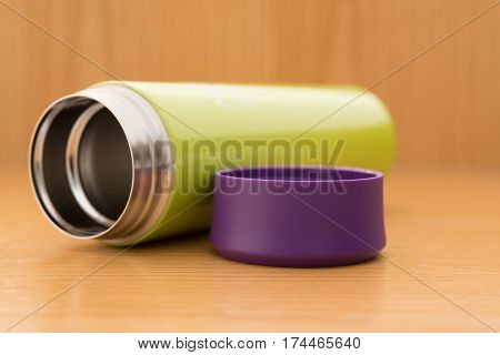 green vacuum tumbler on a wood table