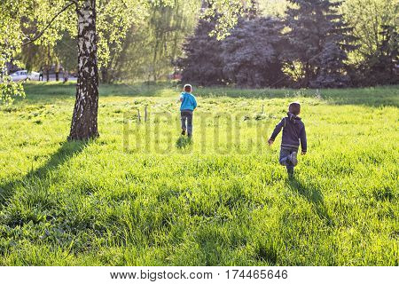 Two boys run off into the distance in the park. Happy joyful kids running on the grass in the park. Spring Park. Park spring summer sunlight.