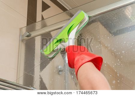 male cleaning glass with brush and chemical sprqy concept of domestic cleaning