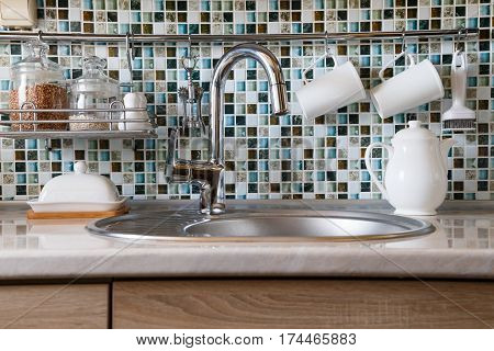 Kitchen interior and kitchen utensils. Kitchen table with various white dishes and built-in kitchen sink and a metallic paint faucet.