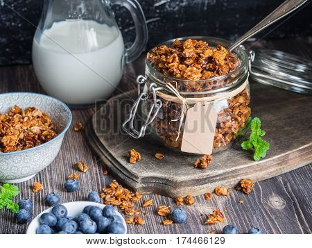 Baked granola and berries in small bowls.. Granola baked with nuts and honey.