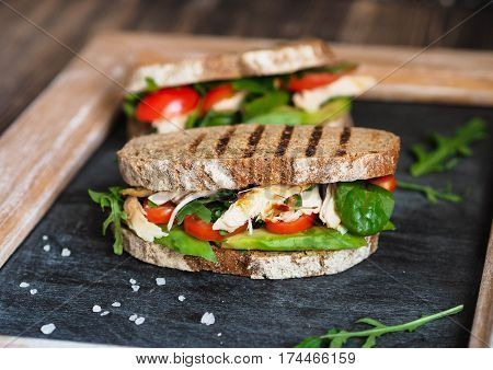 Homemade sandwich with avocado, arugula, tomatoes and grilled chicken