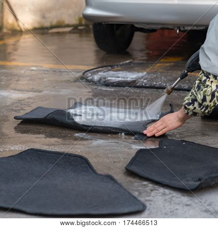 washing carpets for a car with soapy water