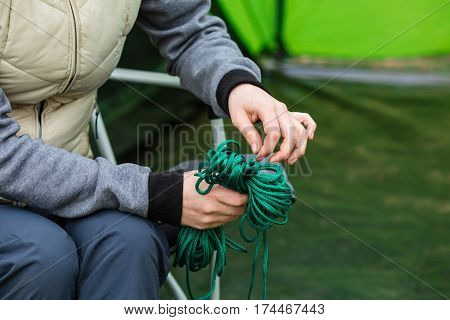 female hand holding rope skein, close-up. accessories and equipment for for camping and outdoor activities.