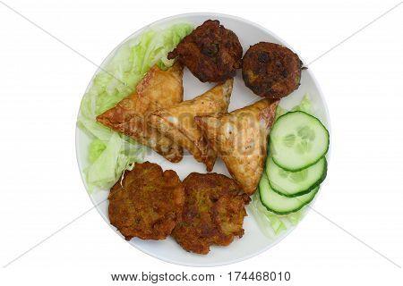 Indian snacks including samosas, onion bhajis and pakoras on plate isolated on white