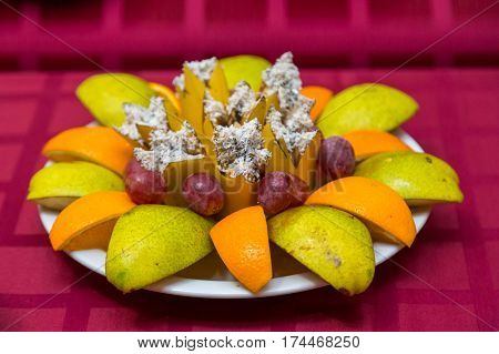 Fruits on plate on white plate. Bananas, apples , pineapple, oranges. Assorted fruits on the plate. Flat lay. Vegan. Healthy food concept.
