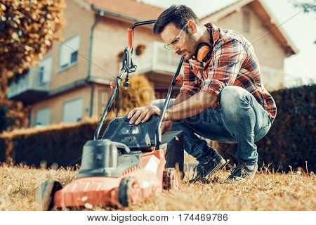 Man cutting grass in his yard with lawn mower.