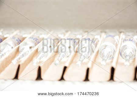 Row of transparent medical ampules in package. Close up